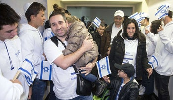 A French family, making aliyah (immigration to Israel), are welcomed by Israelis waving national flags upon their arrival at Ben Gurion International Airport, Dec. 8, 2015.