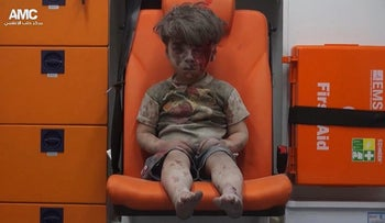 FILE - In this Aug. 17, 2016 file frame grab taken from video provided by the Syrian anti-government activist group Aleppo Media Center (AMC), 5-year-old Omran Daqneesh sits in an ambulance after being pulled out of a building hit by an airstrike in Aleppo, Syria. Hundreds of thousands of amateur videos uploaded to YouTube that document every heartbeat of the Syrian war, have been removed as the tech giant applies new technology to rein in violent content on the internet, causing a panic among the activists for their visual history. (Aleppo Media Center via AP, File)