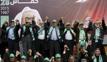 A group of seven Hamas leaders on top of a stage joining and raising their hands as they take part in a rally marking the 28th anniversary of Hamas' founding, in Gaza City December 14, 2015. About 10 people are below the stage, also lined up and joining hands.