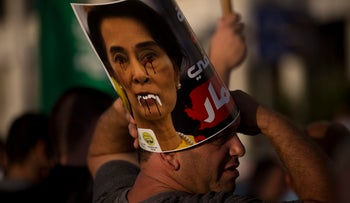 A member of the Islamic Movement in Israel displays a defaced poster of Myanmar's Aung San Suu Kyi during a demonstration to condemn Myanmar's treatment of the Rohingya, Tel Aviv, September 11, 2017