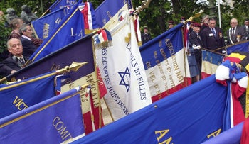 Veterans and former deportees display flags at a ceremony to remember victims of racism and antisemitism committed by the French state during World War II, in Paris, Sunday, July 18, 2004.