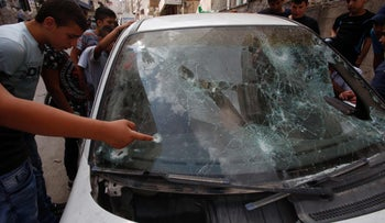 Palestinians look at a damaged car belonging to a Palestinian man who was killed by Israeli security forces after he attempted to ram his vehicle into Israeli border guards  early in the morning in the Shufat refugee camp, in east Jerusalem, on September 5, 2016.