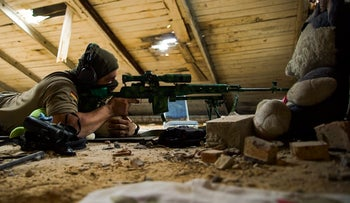 In this photo taken on Thursday, Aug. 25, 2016, a Ukrainian sniper who gave his name only as Corporal takes his position in the village of Marinka, near Donetsk, eastern Ukraine.