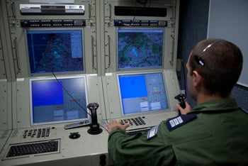 An operator in an Israel Air Force base pilots an Israeli Heron (Eitan) drone, April 5, 2011. A man in an army uniform sits in front of a bank of four monitors showing coordinates and a map, one hand on a specialized computer keyboard and the other on a joystick.