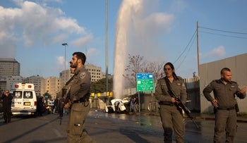Israeli policemen stand guard in front of the car of a Palestinian attacker who was shot dead after driving into Israelis at a bus stop on December 14, 2015 in Jerusalem.