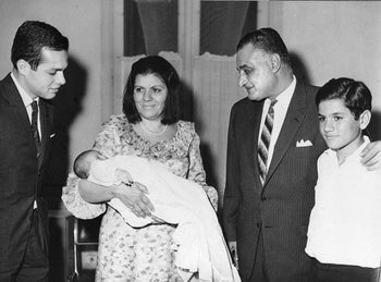 Gamal Abdel Nasser, president of the United Arab Republic, takes his first look at his second grandson, Gamal Marwan, born to his daughter Mona a few days ago, in Cairo, April 27, 1967. The president's wife Tahia holds their grandchild while the baby's father Ashraf Marwan looks on at left. At right is Nasser's youngest son Abdel Hakim.