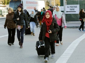 Women wearing hijabs pull their luggage as they walk to a bus stop in New York, November 25, 2015.
