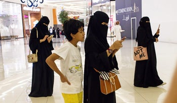 Women use their smartphones while visiting the Al Yasmin mall in Jeddah, Saudi Arabia, on Sunday, Aug. 6, 2017. After relying on oil to fuel its economy for more than half a century, Saudi Arabia is turning to its other abundant natural resource to take it beyond the oil age -- desert.
