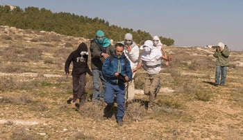 Masked youths attacking members of the NGO Ta'ayush and colleagues from abroad, the South Hebron Hills, January 7, 2017.