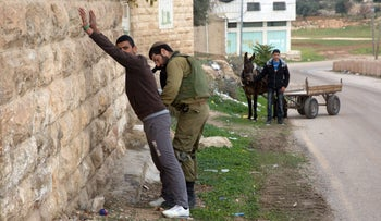 A Palestinian is checked by Israeli soldiers patrolling the streets of the West Bank city of Hebron on December 15, 2015.