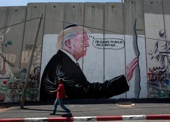 A mural resembling the work of elusive artist Banksy depicting President Donald Trump wearing a Jewish skullcap on Israel's West Bank separation barrier, Bethlehem. Aug. 4, 2017