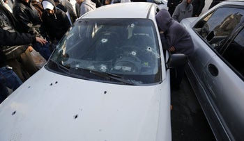 Palestinians stand next to a car, used by Palestinians in an attempted ramming attack against Israeli soldiers, in the Qalandiya refugee camp near the West Bank city of Ramallah on December 16, 2015.