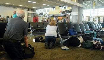 Passengers take cover during Fort Lauderdale Airport shooting attack on January 6, 2017.