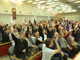 Histadrut members raise their hands to show support for a general strike.