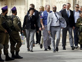 Nickolay Mladenov, the United Nations Secretary-General Special Representative to the Middle East (3rd R), looks at Israeli soldiers during his visit to the West Bank city of Hebron November 4, 2015.