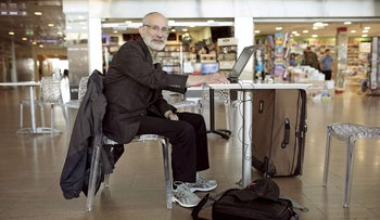 Jonathan Rosenberg, a 63-year-old man from Silver Spring, Maryland sits at a table in the airport in front of his laptop computer.