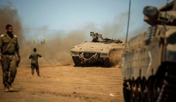 Israeli soldiers manuever a Namer armored personnel carrier and Merkava tanks during the last day of a military exercise in the Golan Heights on September 13, 2017.