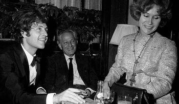 Left: French singer Joe Dassin, smoking a cigar at the table of a bar; center, his father, the American director Jules Dassin; right, his mother Beatrice Launer. Paris, 1970.