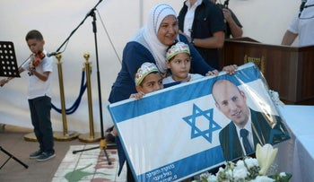 Students and parents pose for a photo with a poster bearing Education Minister Naftali Bennett's image on the first day of school in Tamra, September 2016.
