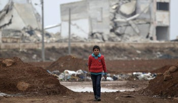 A boy walking in front of damaged buildings in the northern Syrian rebel-held town of al-Rai, Syria January 5, 2017.