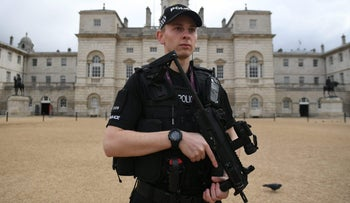 An armed police officer stands guard outside the Horse Guards Parade in central London on September 16, 2017.