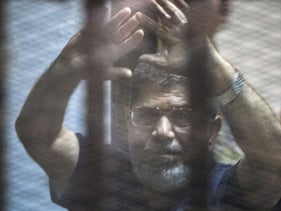 Egypt's deposed Islamist president Mohamed Morsi raises his hands from behind the defendant's cage as the judge reads out his verdict sentencing him and more than 100 other defendants to death at the police academy in Cairo on May 16, 2015.