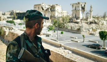 A Syrian soldier guards streets in Aleppo, Syria, on Tuesday, Sept. 12, 2017.