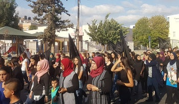 Protesters wave black flags during the march against violence against women in Majd al-Krum, September 16, 2017.