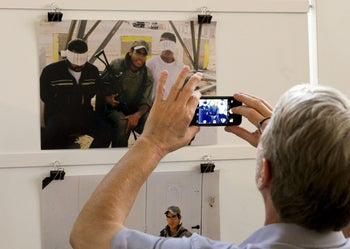 A visitor takes a picture at the 'Breaking the Silence' exhibition at the Kulturhaus Helferei in Zurich, June 8, 2015.