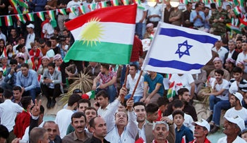 A Kurdish man holds Israeli and Kurdish flags during a rally for the upcoming September 25th independence referendum in Erbil, Iraq, September 16, 2017