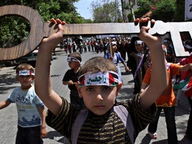 """A Palestinian boy holds a symbolic key to the house his family left in the 1948 war, now under Israeli control, and wears a headband with the Arabic for """"We are coming back"""". Gaza City, May 12, 2011"""