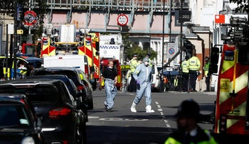 Police forensic officers walk within a cordon near where an incident happened, that police say they are investigating as a terrorist attack, at Parsons Green subway station in London, Sept. 15, 2017.