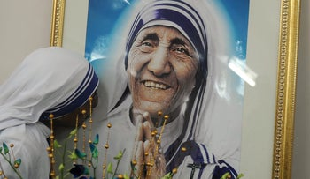 A nun belonging to the order of the Missionaries of Charity kisses a picture of Mother Teresa during a mass service, September 5, 2012.