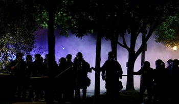 Law enforcement officials walk down a residential street after firing tear gas at protesters in St. Louis, Missouri, September 15, 2017.