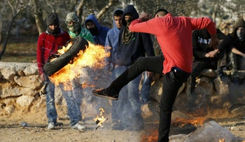 A Palestinian protester kicks a burning tire during clashes between Palestinian youth and the Israeli army in Silwad, December 11, 2015.