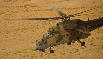In this Friday, Sept. 15, 2017 photo Russian military helicopter flies over the desert in Deir el-Zor province, Syria. A U.S.-backed force in Syria said a Russian airstrike wounded six of its fighters Saturday near the eastern city of Deir el-Zour while in southeast Syria
