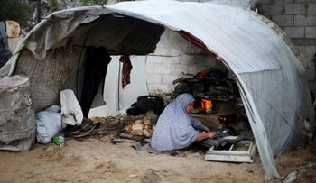 A Palestinian woman bakes bread in a tent outside her dwelling in Khan Younis in the southern Gaza Strip December 19, 2016.