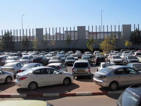 A parking lot with cars at the Kfar Sava train station.