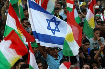 Iraqi Kurds fly an Israeli flag and Kurdish flags during a pro-referendum rally in Erbil, the capital of the autonomous Kurdish region of northern Iraq. September 16, 2017