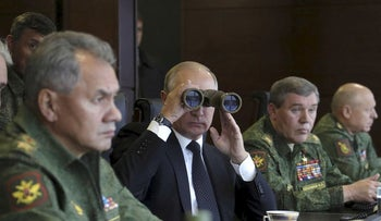Russian President Vladimir Putin uses a pair of binoculars while watching the Zapad-2017 war games, held by Russian and Belarussian servicemen, Russia September 18, 2017
