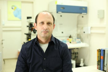 "Dr. Noam Shomron in his lab. Picture shows mildly smiling scientist with high forehead and dark blue shirt, top button undone, over a white undershirt. On the right we see some books, including one clearly titled ""Genetics,"" and in the background we see a laboratory equipment."