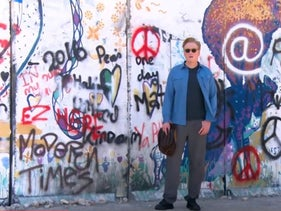 A screenshot shows Conan O'Brien standing in front of the separation barrier in the West Bank.