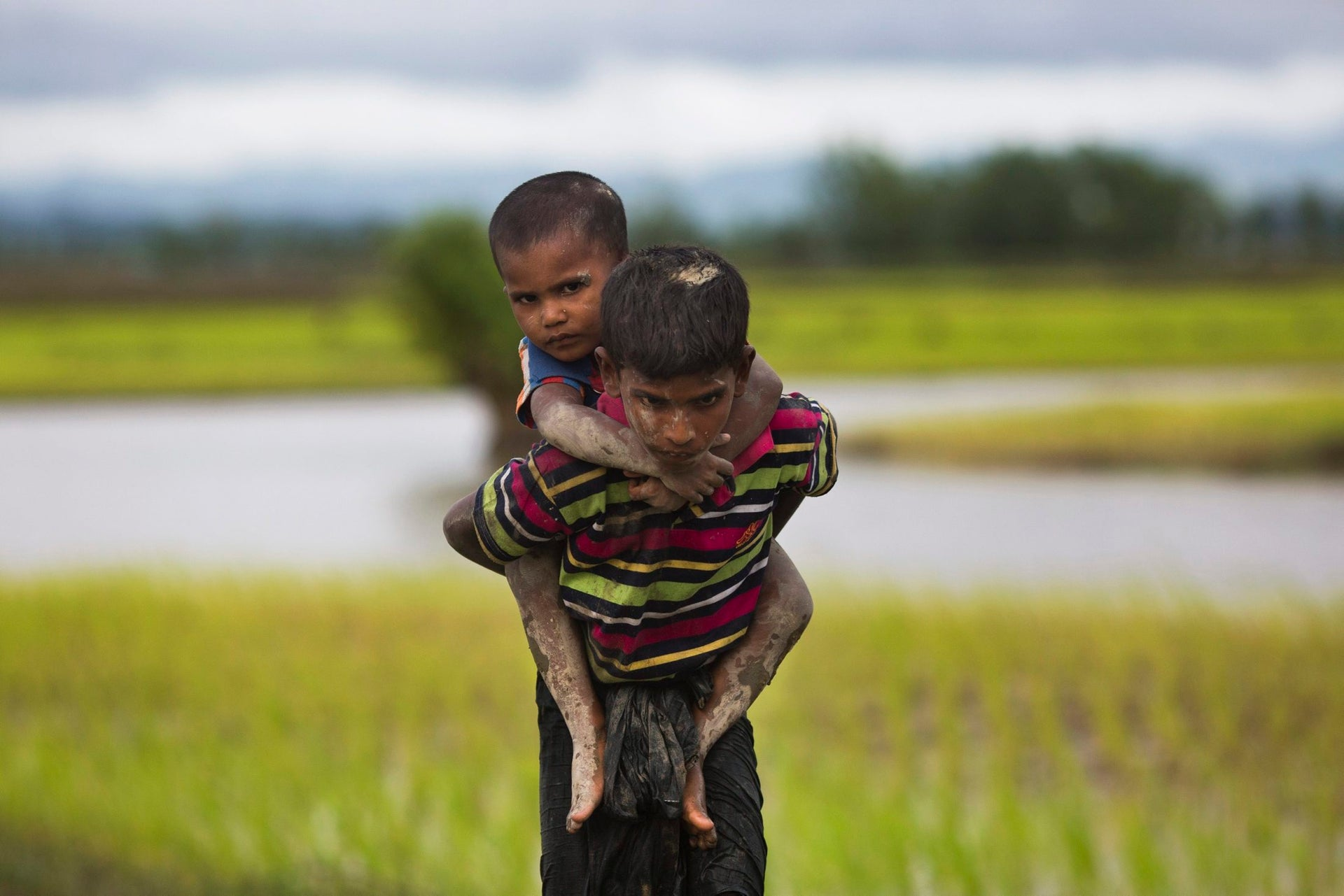In this Sept. 1, 2017, file photo, a young Rohingya Muslim boy from Myanmar carries a child on his back after crossing over to the Bangladesh side of the border near Cox's Bazar's Teknaf area.