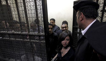 NGO employees stand in a cage during their trial in Cairo, Egypt, March 2012.