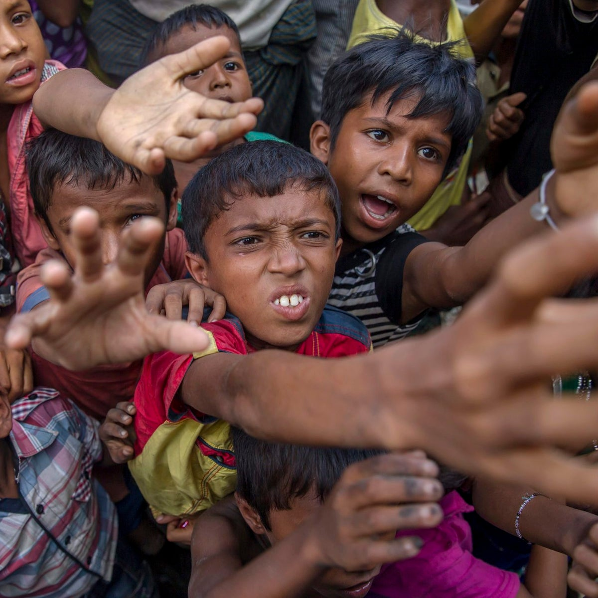 Rohingya Muslim children stretch out their arms out to collect chocolates and milk distributed by Bangladeshi men at Taiy Khali refugee camp, Bangladesh, September 21, 2017.