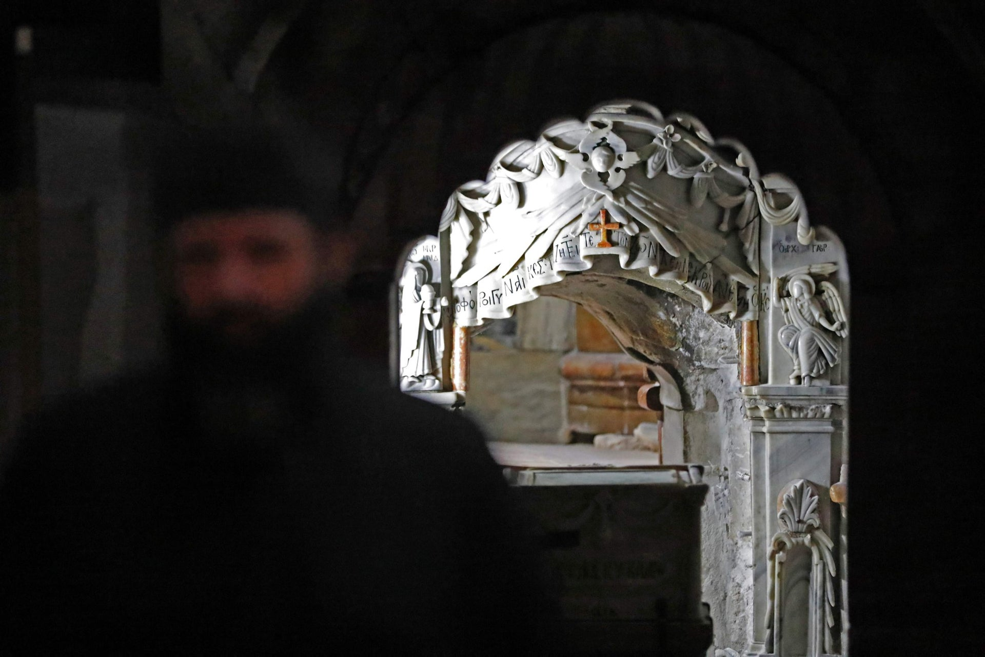 Greek Orthodox and Franciscan priests stand behind a panel placed next to the Tomb of Jesus at the Church of the Holy Sepulchre in Jerusalem's Old City on October 28, 2016.