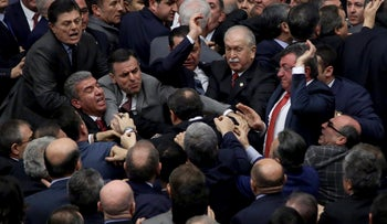 Ruling Justice and Development Party and main opposition Republican People's Party legislators scuffle in Turkey's parliament in Ankara, Turkey, Wednesday, Jan. 11, 2017.