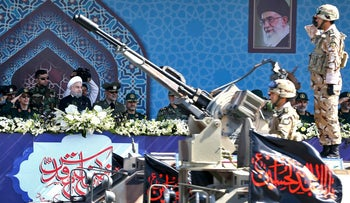 Iran's President Hassan Rouhani, center, reviews a military parade during the 37th anniversary of Iraq's 1980 invasion of Iran, in front of the shrine of the late revolutionary founder, Ayatollah Khomeini, just outside Tehran, Iran, Friday, Sept. 22, 2017.