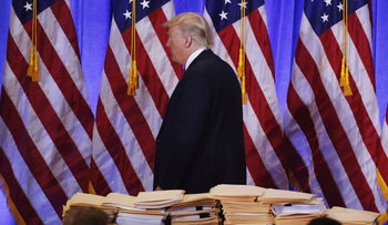 U.S. President-elect Donald Trump walks past a pile of papers during a news conference in the lobby of Trump Tower in Manhattan, New York City, U.S., January 11, 2017.