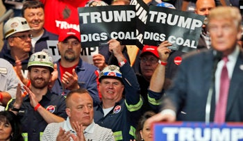 In this May 5, 2016 photo,coal miners wave signs as Republican presidential candidate Donald Trump speaks during a rally in Charleston, W.Va.